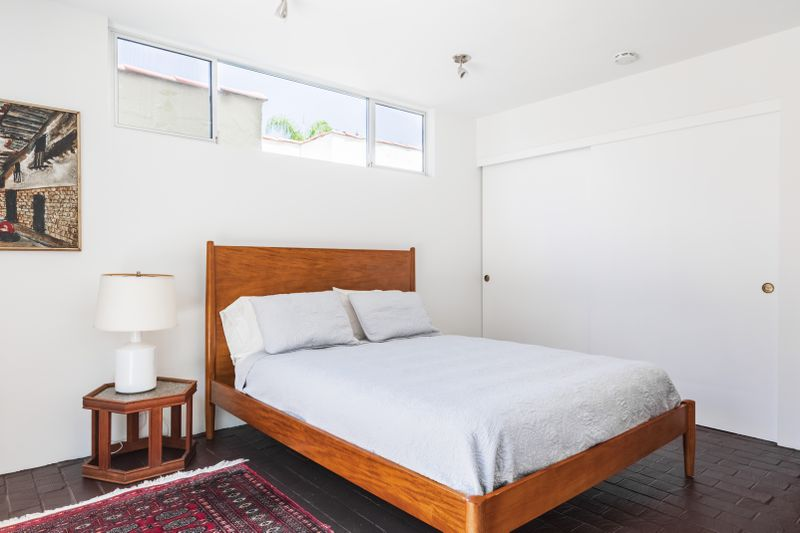 Bright bedroom with white walls and a wood platform bed.