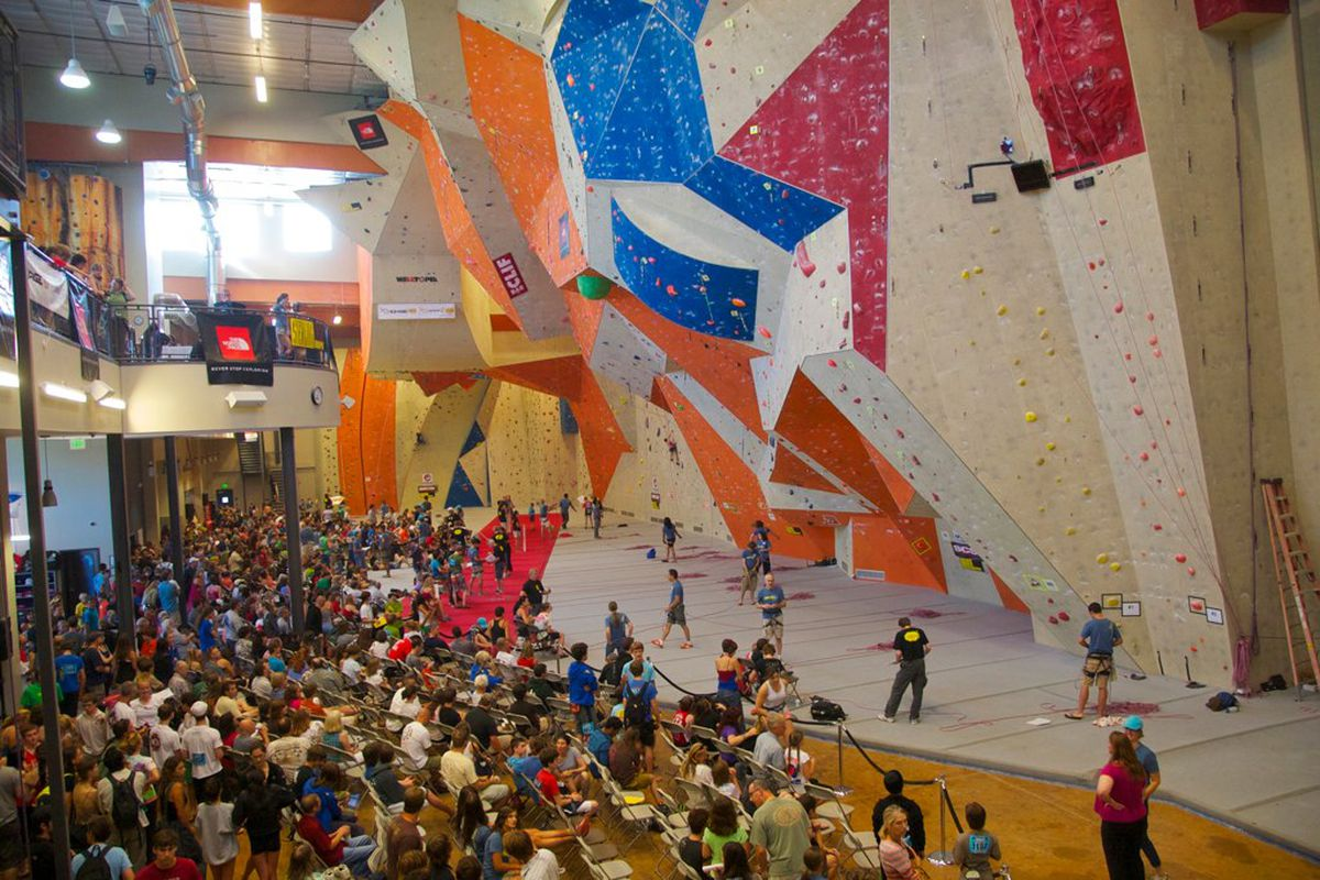 People watch as others climb tall walls.