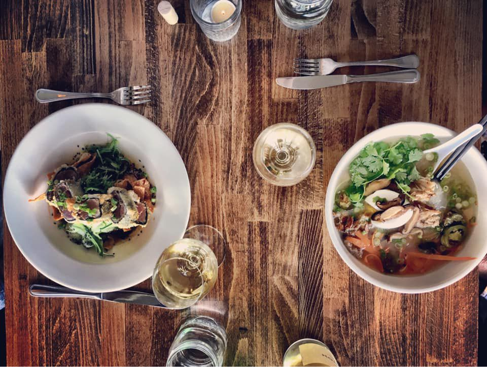 A top-down image of food at Haven, with a soup on the right, along with several cocktails