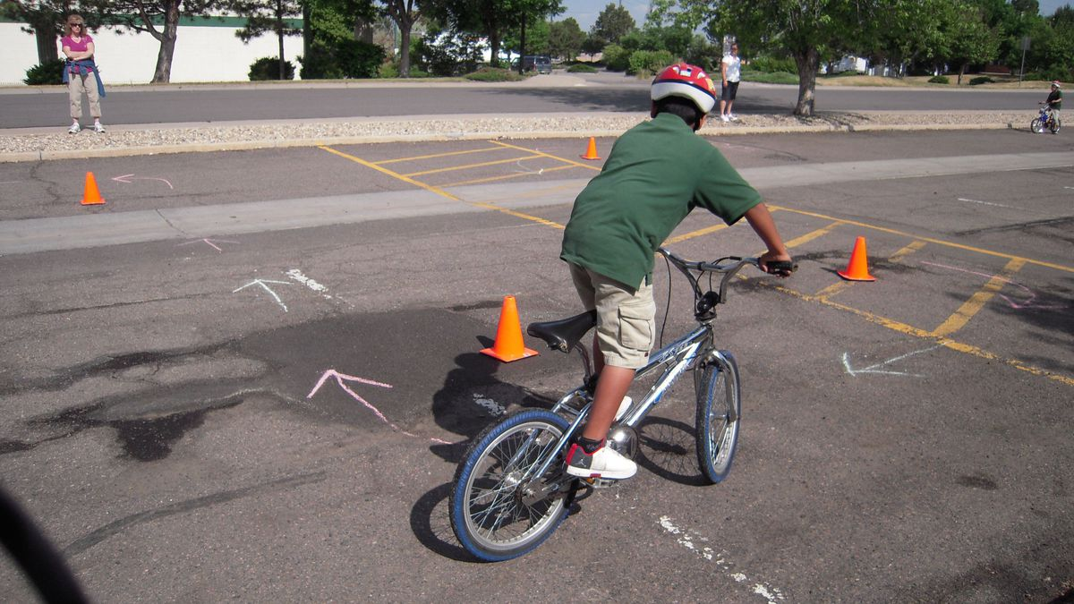 A fourth-grader at Aurora's AXL Academy weaves his bike through cones during the school's bike rodeo to promote biking to school safely.