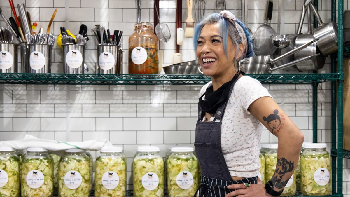 A woman with blue hair tied up in a bandana stands in front of a row of fermented vegetables and kimchis at Mama Dút on SE Morrison