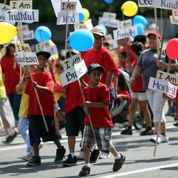 People march with the Granger North Stake float in the Days of '47 Youth Parade in Salt Lake City on Saturday, July 20, 2013.