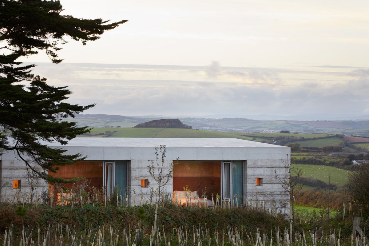 Concrete house on green rolling hill