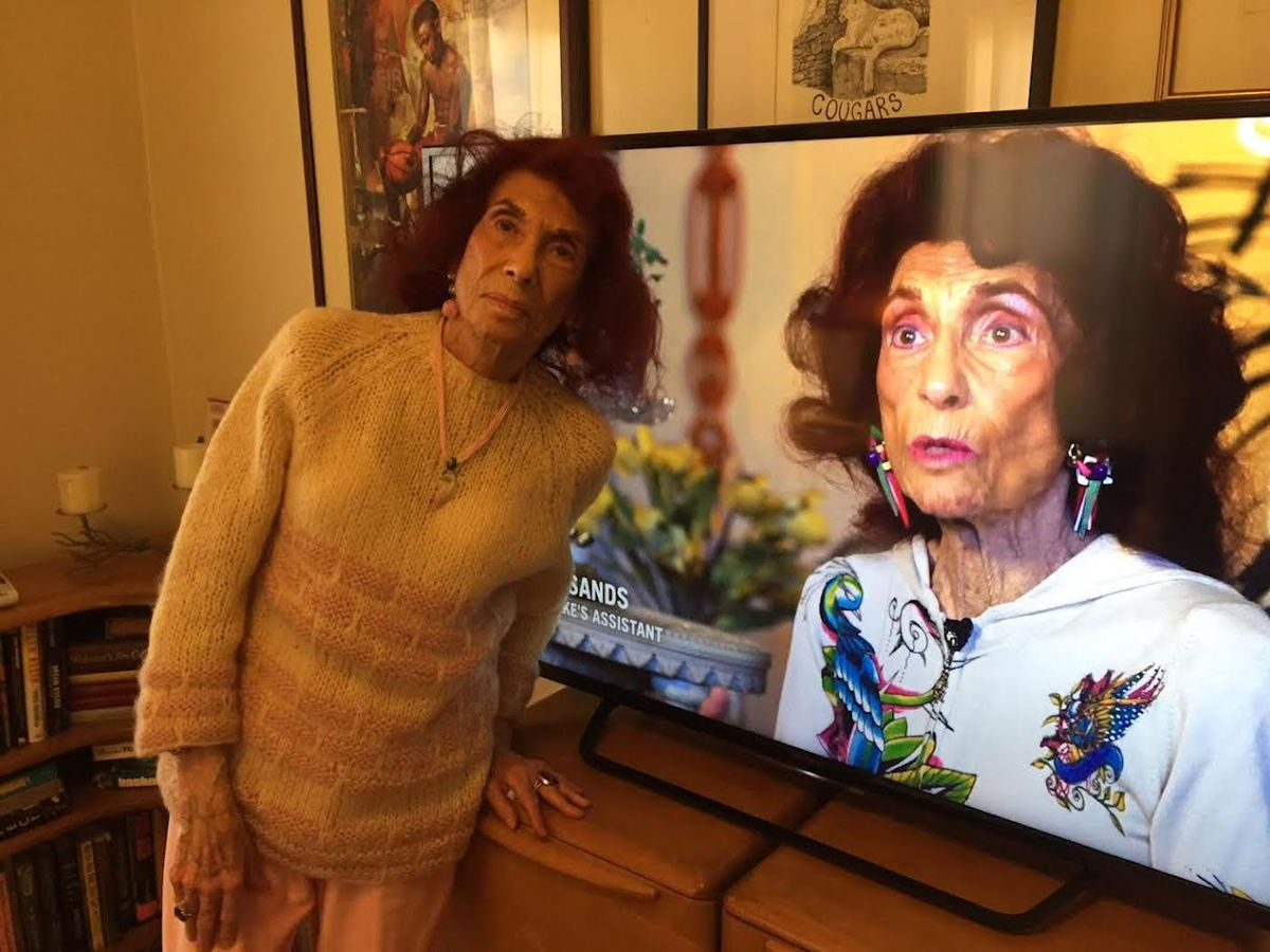"""Zelda Sands standing in front of a TV playing a documentary for which she was interviewed, """"Lady You Shot Me: the Life and Times of Sam Cooke."""""""