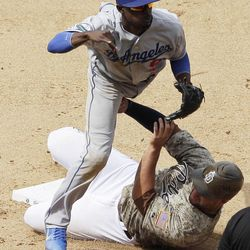Los Angeles Dodgers shortstop Dee Gordon, above, jumps over San Diego Padres' Yonder Alonso after getting the out at second after a hit by Jason Bartlett during a baseball game Sunday, April 8, 2012, in San Diego. Bartlett was safe at first.