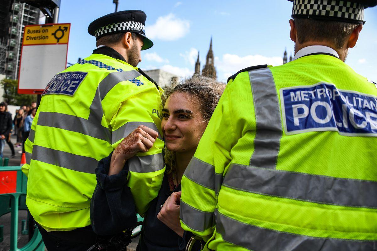 London police officers arrest a smiling Extinction Rebellion activist.