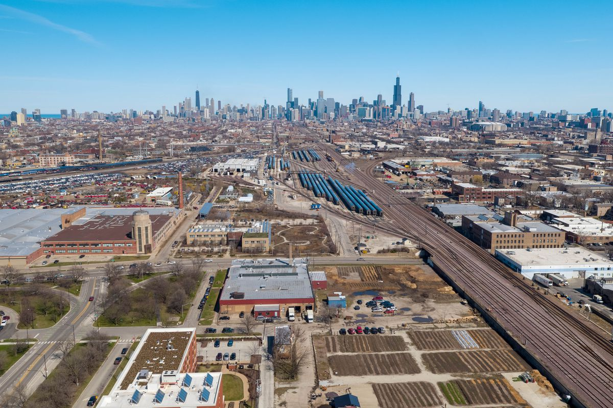An overhead view of businesses and train tracks with a row of tall buildings in the distance.