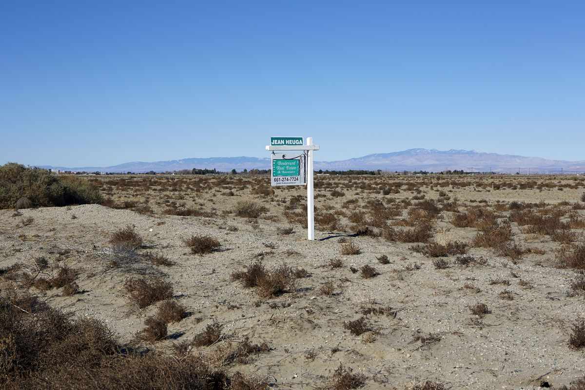 A real estate sign in the middle of a vast stretch of land.