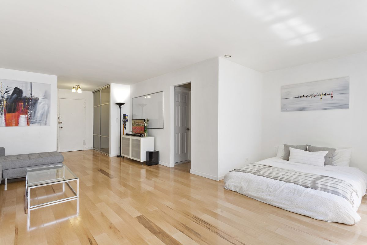 A living area with hardwood floors, a bed, white walls, and a glass coffee table.