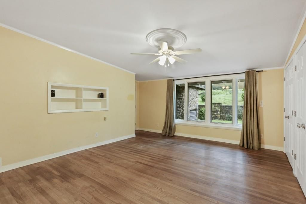 A yellow bedroom with curtains and ceiling fan.
