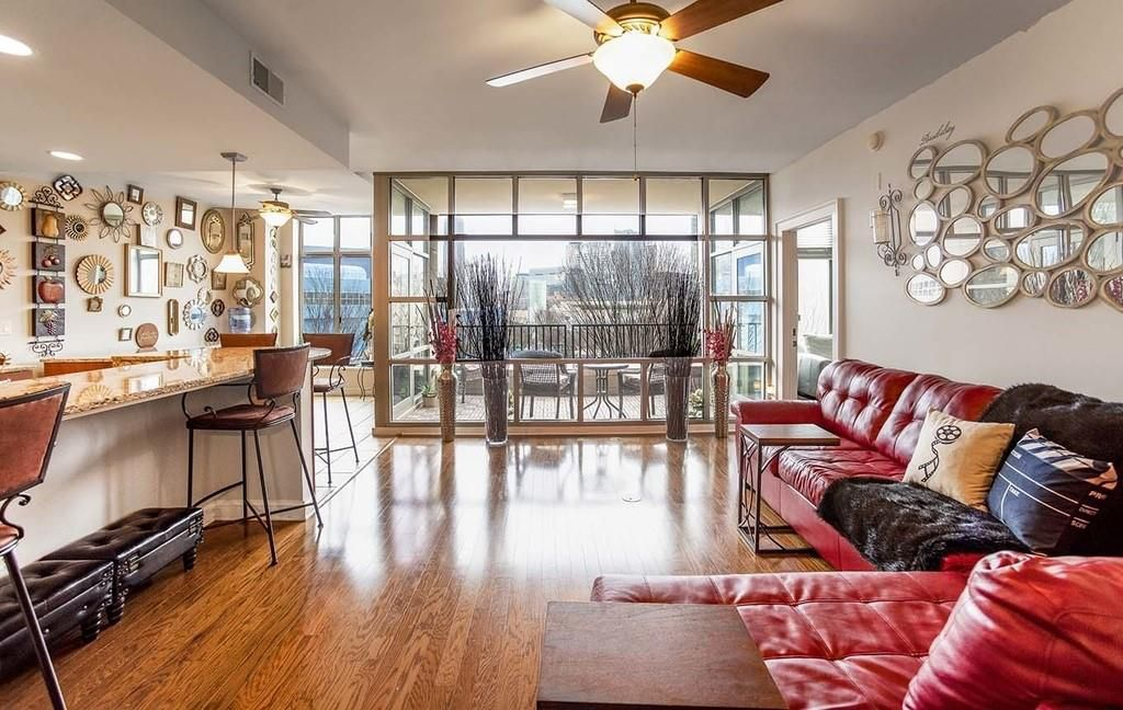 Expansive living space with kitchen to the left and floor-to-ceiling windows looking out to balcony in back.