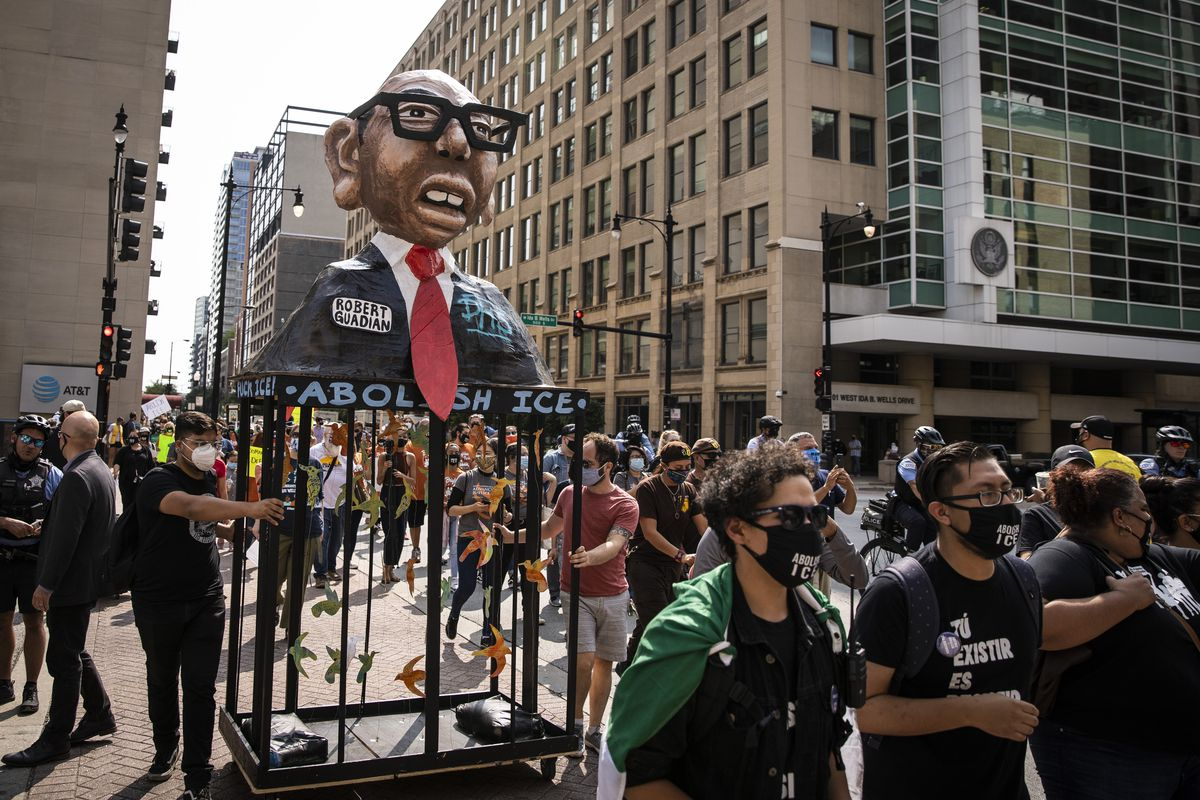 """Activists with immigrant rights organizations and their supporters push a float of U.S. Immigration and Customs Enforcement Chicago Field Office Director Robert Guadian as they march to Federal Plaza in the Loop, marking the date on which ICE would have begun its now-postponed """"Citizens Academy"""" Tuesday afternoon, Sept. 15, 2020."""
