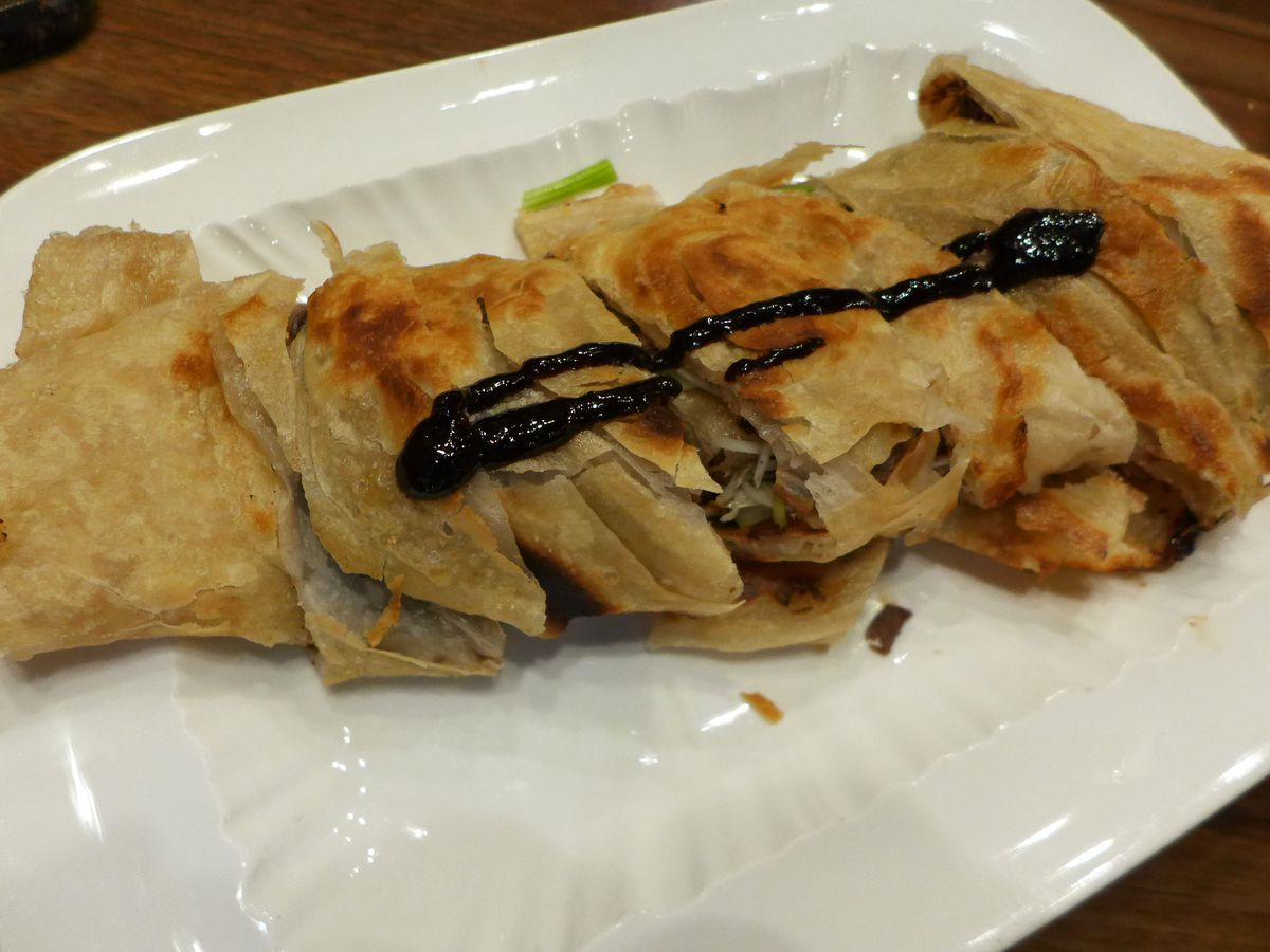 Chinese beef burrito with squiggle of brown sauce on top.