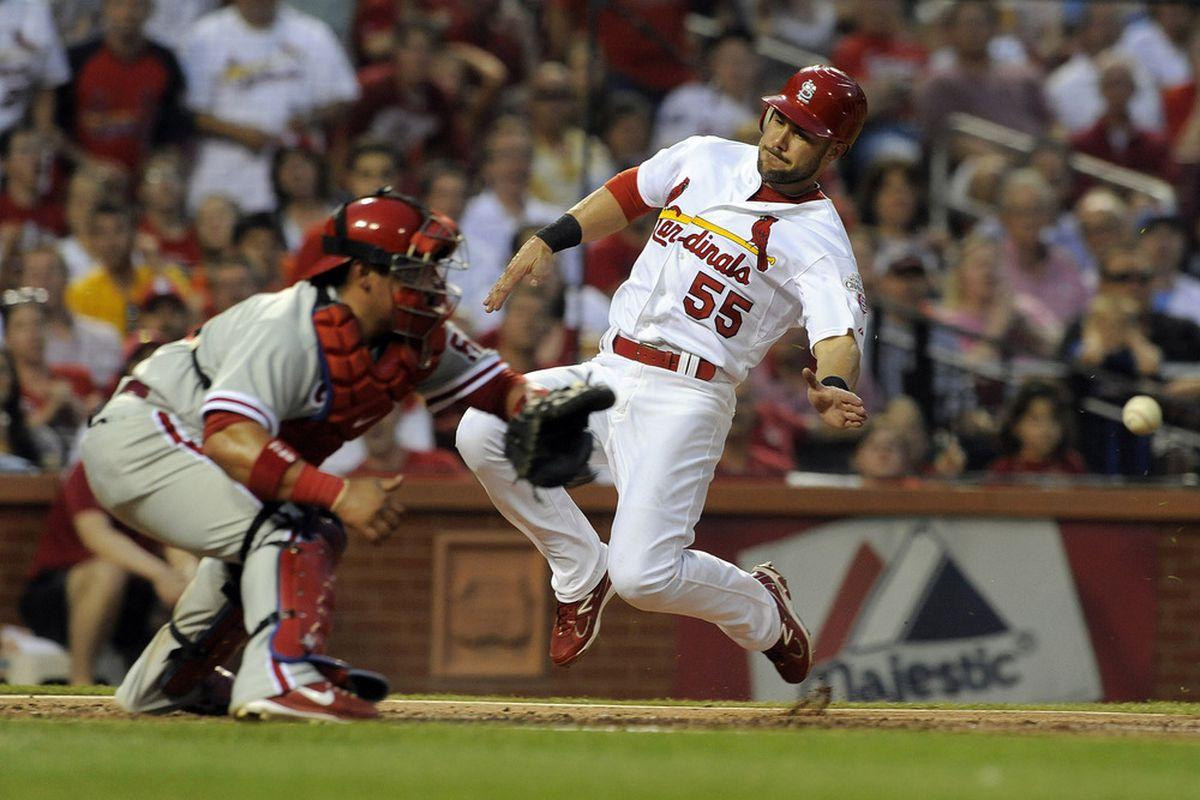 May 24, 2012; St. Louis, MO. USA; St. Louis Cardinals second baseman Skip Schumaker (55) slides past Philadelphia Phillies catcher Carlos Ruiz (51) during the third inning at Busch Stadium. Mandatory Credit: Jeff Curry-US PRESSWIRE