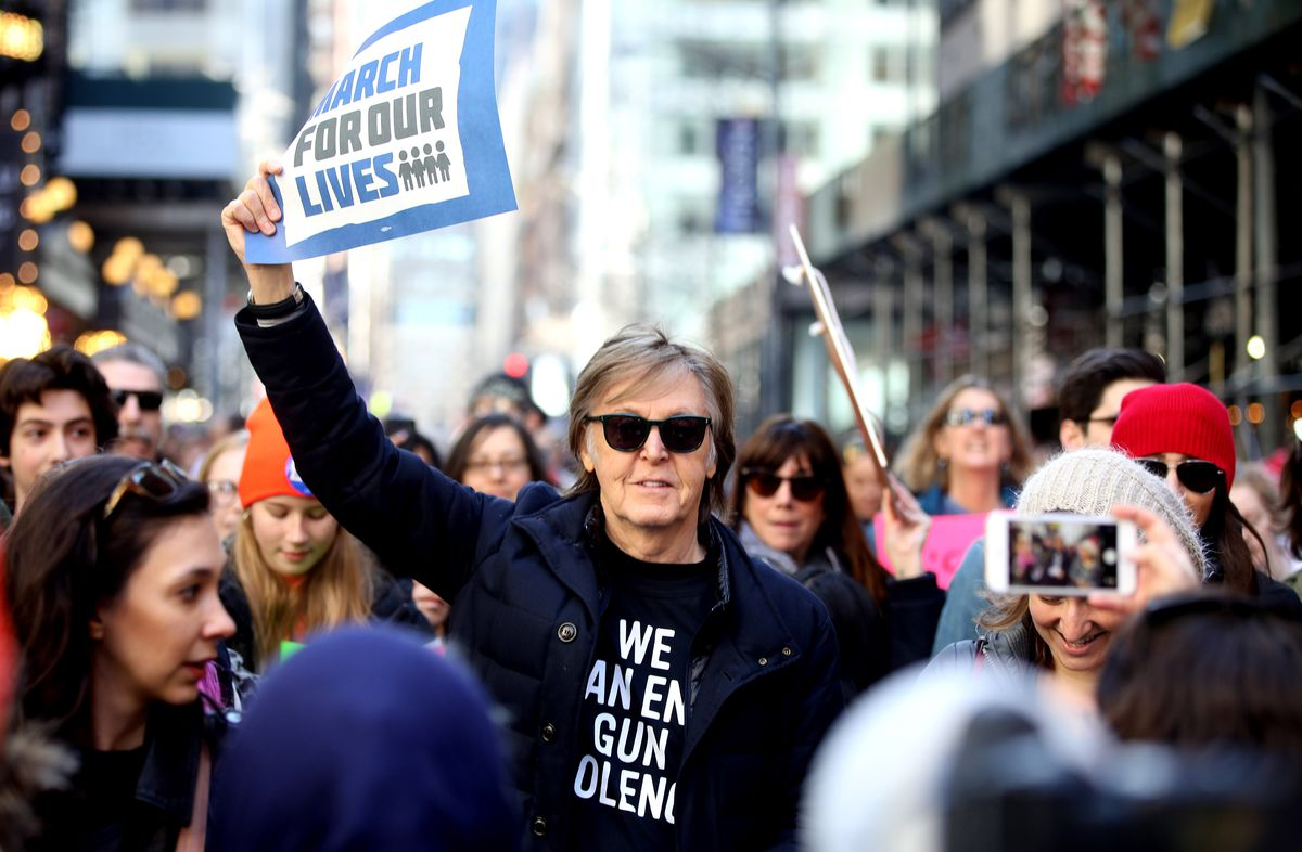 """Ex-Beatle Paul McCartney wears a """"We Can End Gun Violence"""" t-shirt and carries a March for Our Lives"""" sign at the New York City March for Our Lives rally and protest."""