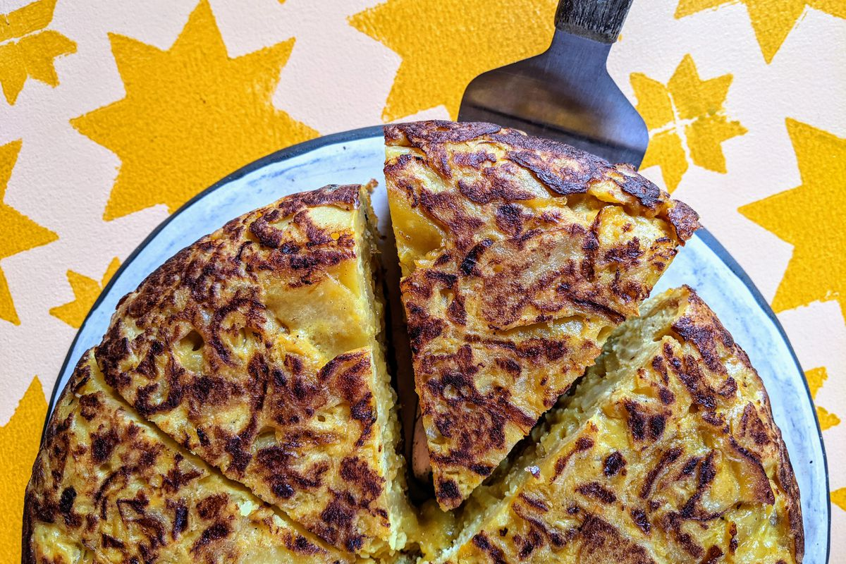 A triangular slice of Spanish omelet gets pulled from a plate.