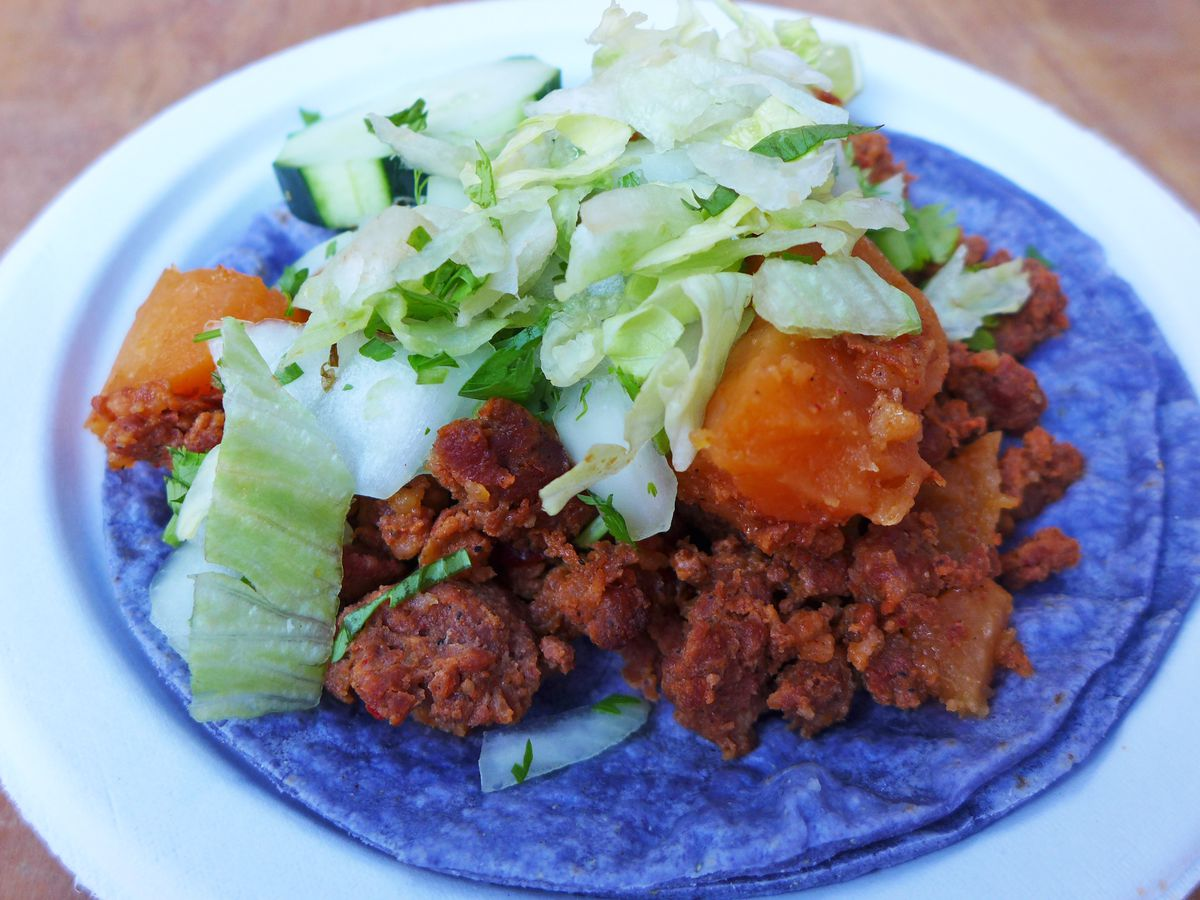 Crumbled sausage and orange potato cubes on a pair of soft bright blue corn tortillas.