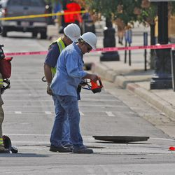Rocky Mountain Power employees and firefighters stand near one of two manhole covers that were blown off near the corner of 300 South and 200 East Monday, Aug. 13, 2012, in Salt Lake City.