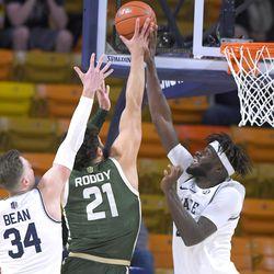 Utah State center Neemias Queta blocks the shot of Colorado State guard David Roddy (21) as Utah State forward Justin Bean (34) helps defend during the first half of an NCAA college basketball game Thursday, Jan. 21, 2021, in Logan, Utah.