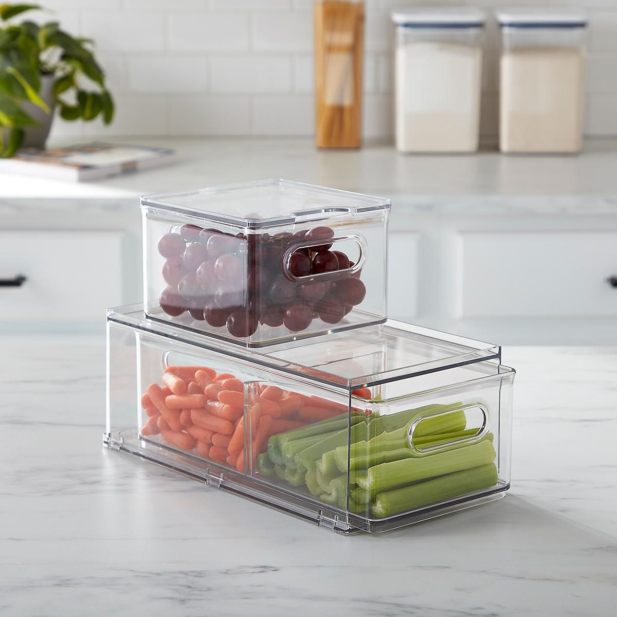 Two stacked clear storage bins containing fruits and vegetables