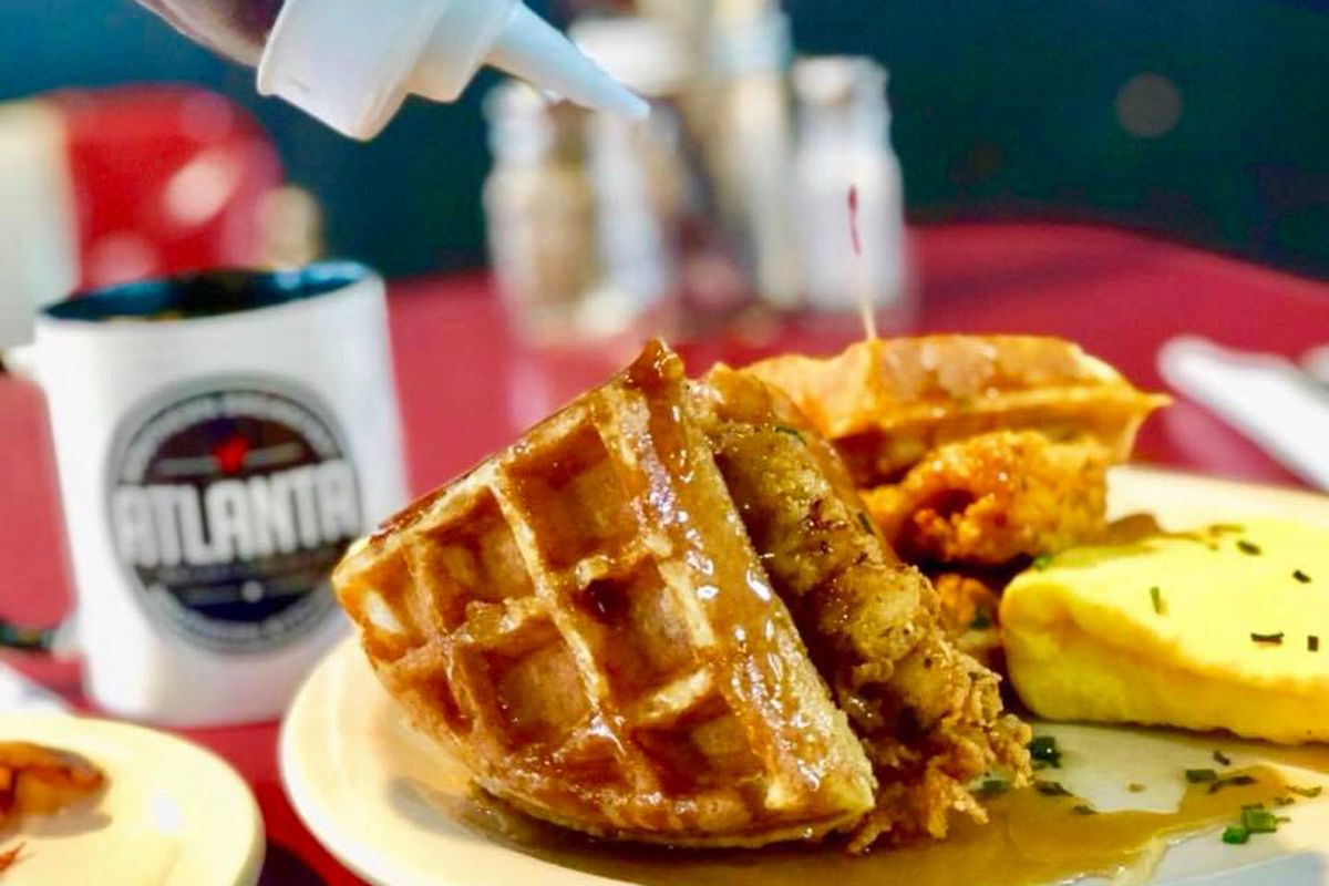 Fried chicken and two triangles of waffles covered in syrup with a folded egg and cup of coffee from Atlanta Breakfast Club