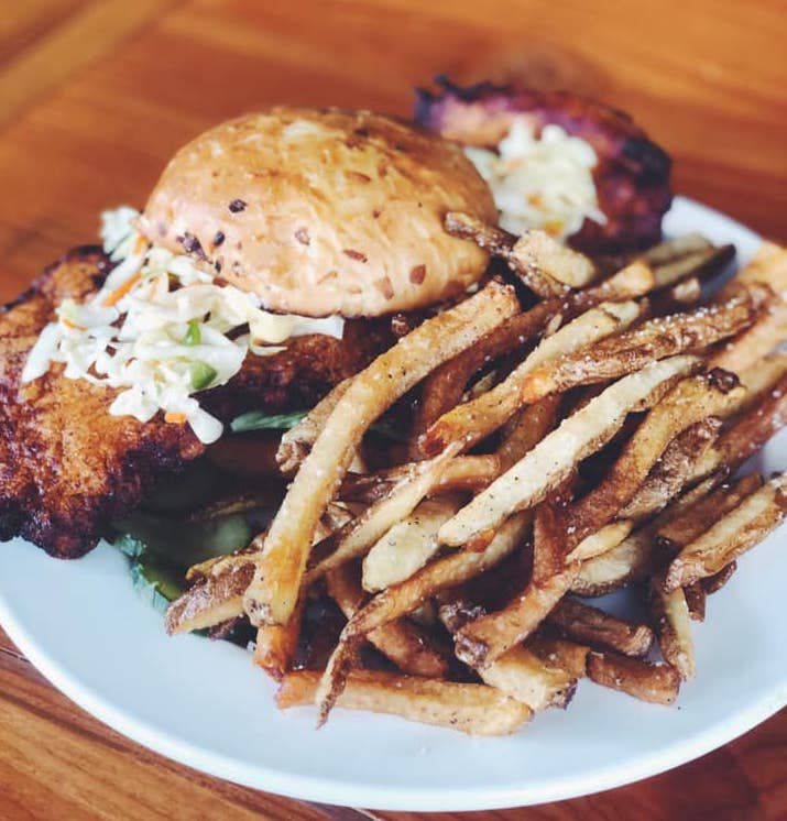 A plate full of fries and a fried chicken sandwich that overtakes its onion bun in size