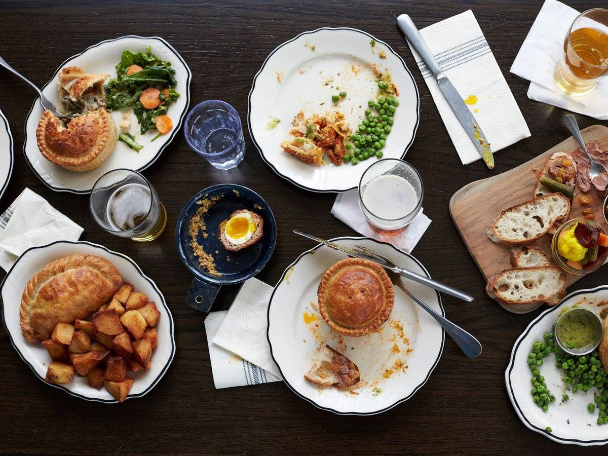 A spread of royal pies, dishes, and drinks on a table.