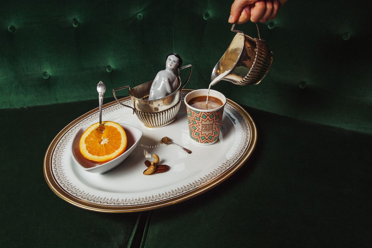 A to-go boat with a half-sliced orange, a hand pouring a cup of coffee from a metal tin, and a ceramic doll