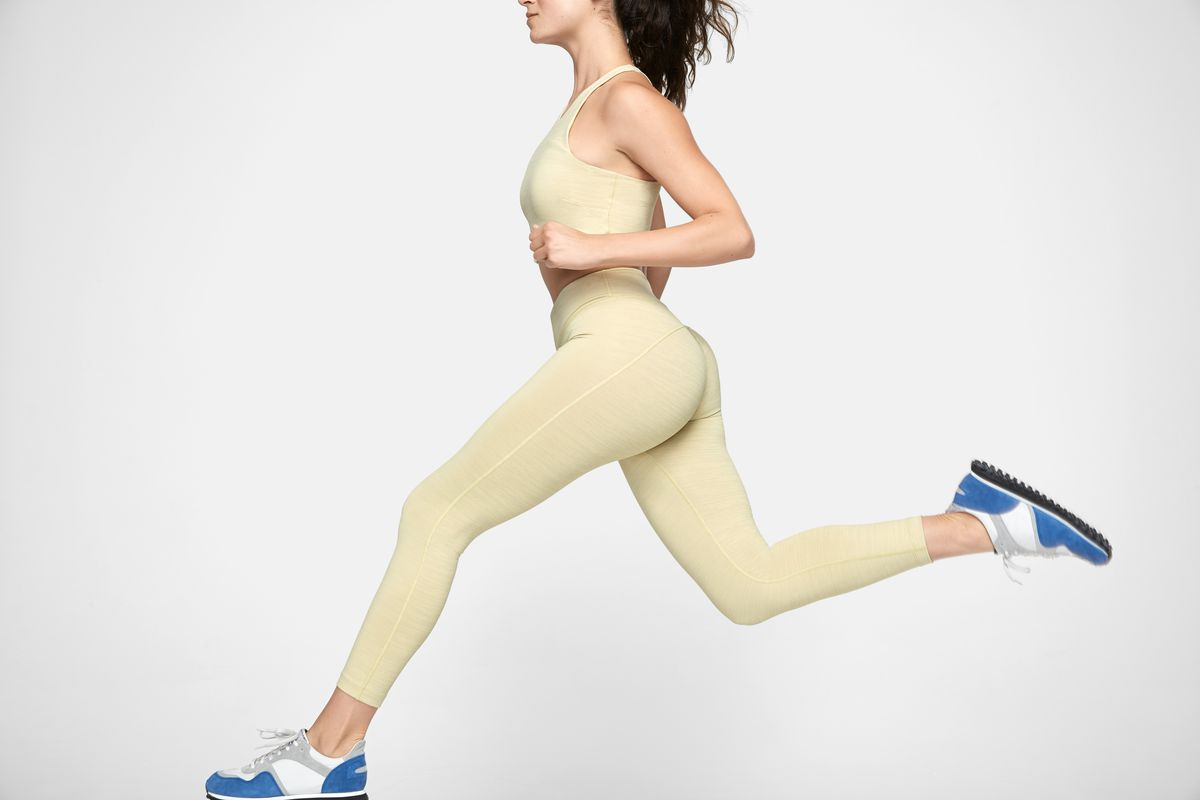 A model wears a pale yellow crop top and legging set, leaping across the screen as though mid-stride.