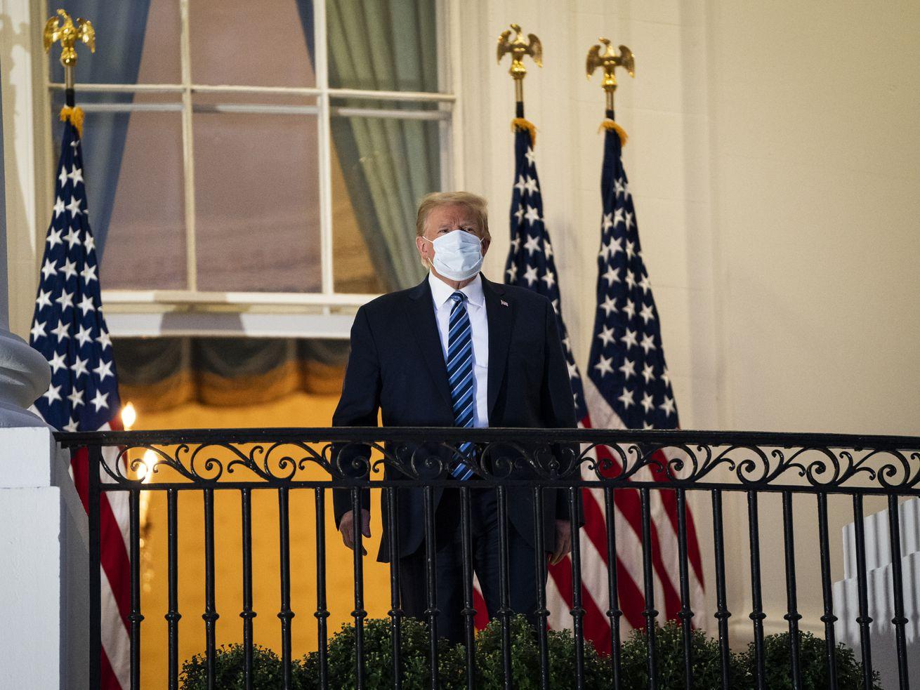 Le président Donald Trump debout sur un balcon de la Maison Blanche portant un masque facial