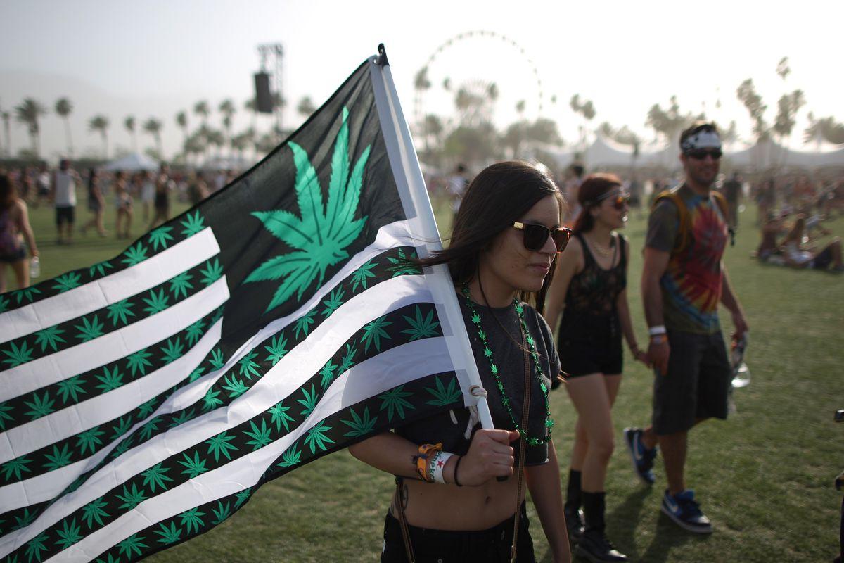 A woman carries a US flag with marijuana symbols.