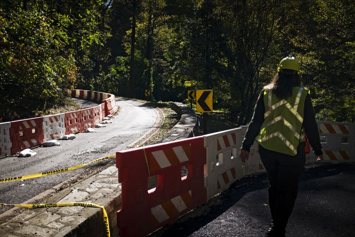 A construction worker is seen from behind with a helmet on walking on a trail adjacent to a vehicular road. There are construction barriers along the paths.