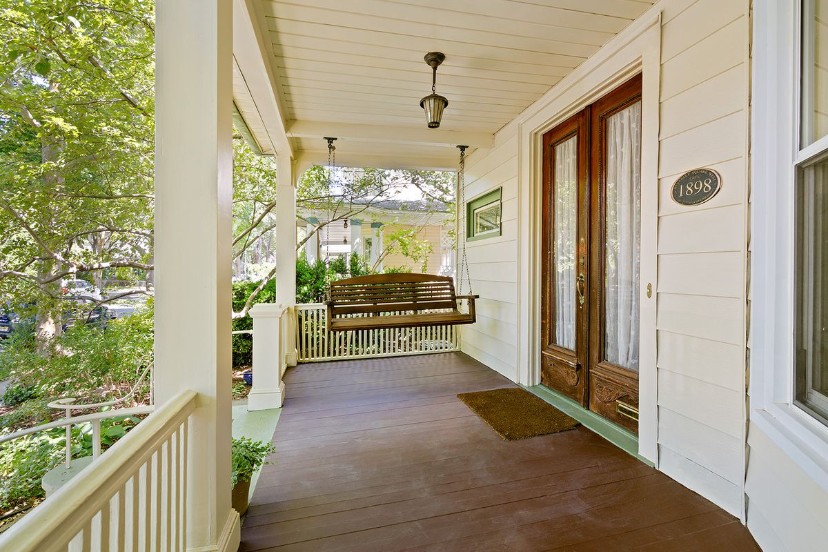 A porch with hardwood floors and a swing.