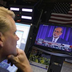 """Federal Reserve Chairman Ben Bernanke is broadcast on a television screen on the trading floor of the New York Stock Exchange, Wednesday, April 25, 2012.  Bernanke says further bond purchases by the Fed remain """"very much on the table"""" if the economy needs further support."""