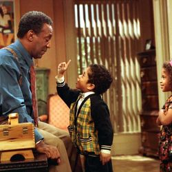 """Bill Cosby, as Dr. Cliff Huxtable of """"The Cosby Show,"""" listens to a point made by his grandson, Gary Gray, as his granddaughter, played by Jessica Vaughn, looks on during taping of the TV show's final episode before a studio audience March 6, 1992. (AP Photo)"""