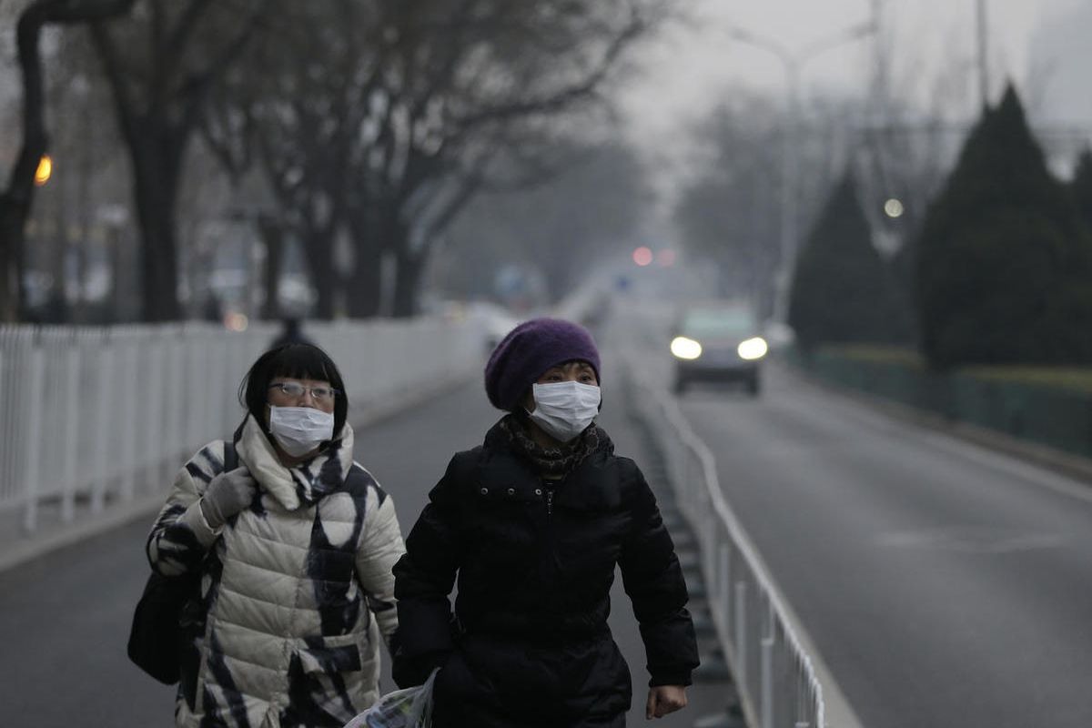 Women wear masks as they walk along a street on a polluted day in Beijing, Sunday, Dec. 13, 2015.
