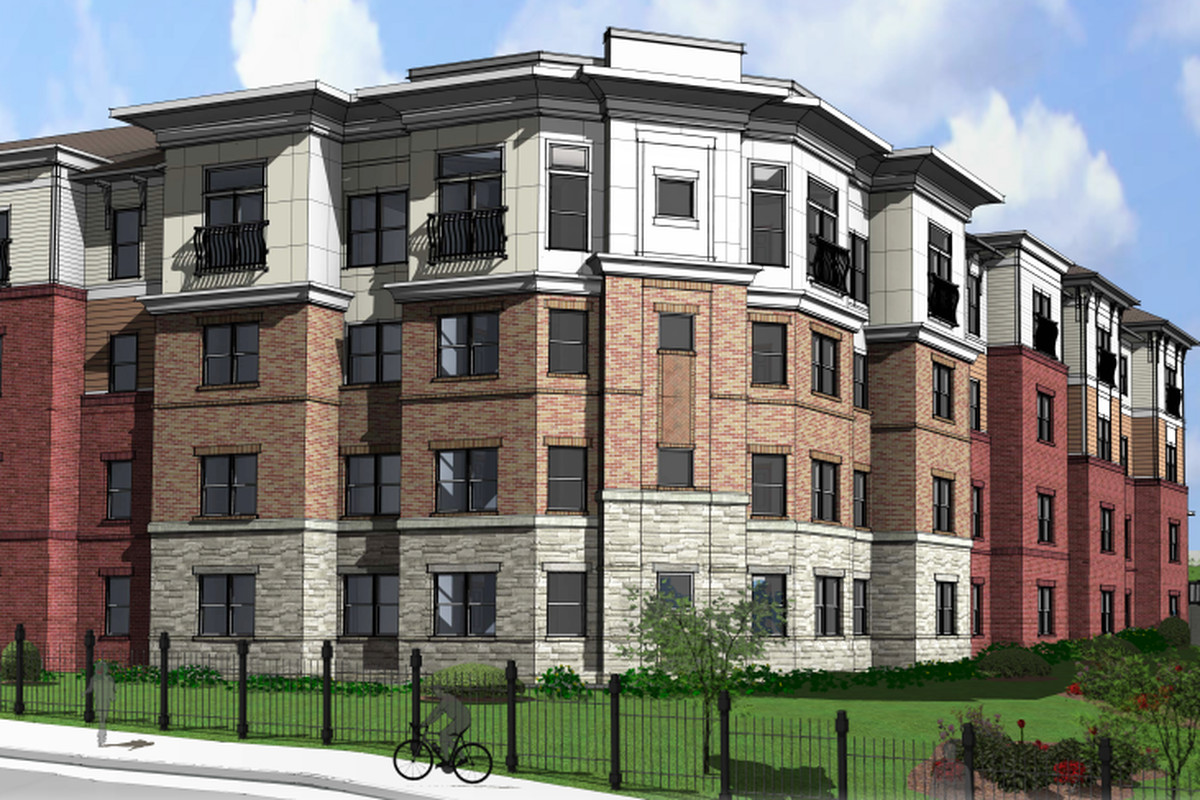 A four-story multi-family residential with stone, brick, and stucco.