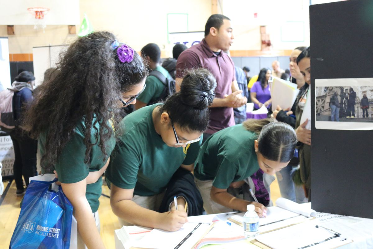 Middle school students write their names down at a high school fair in Brooklyn in 2016.