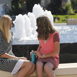 Madie  and Emma Dietz sit by the fountain during the Payson Utah Temple cornerstone ceremony and dedication in Payson  Sunday, June 7, 2015.