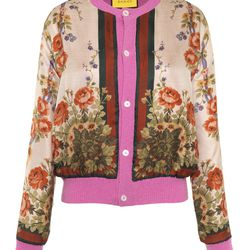 A reversible cashmere and merino wool cardigan with vibrant pink details.