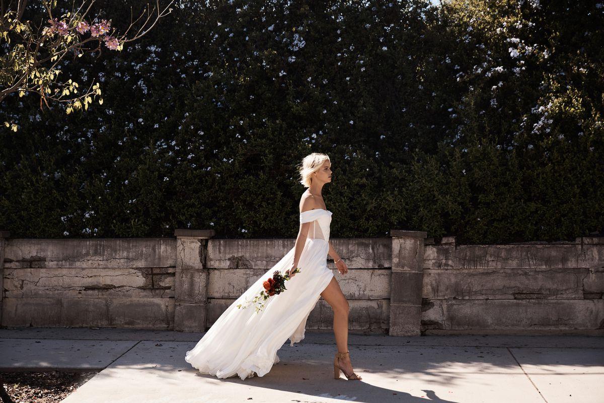 A model walking outside in a Floravere wedding dress