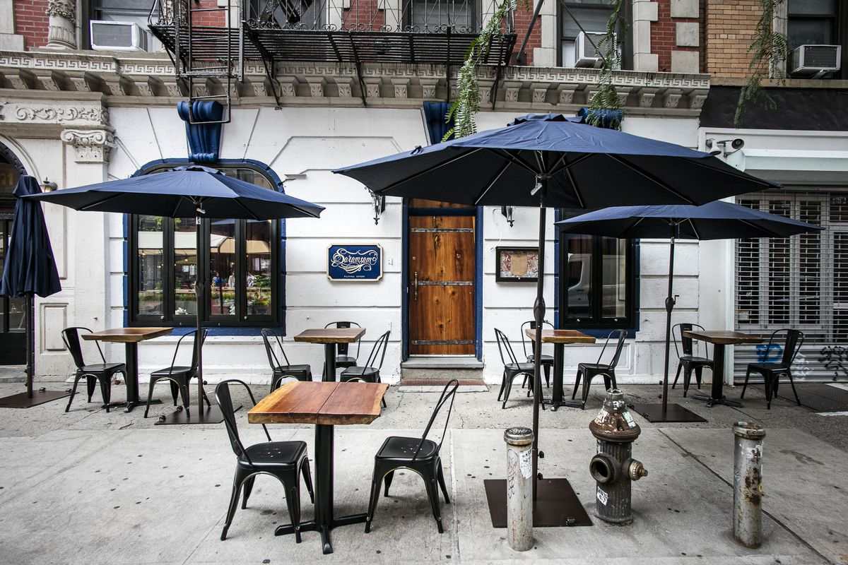 The white exterior of a restaurant with five tables and chairs set up on a sidewalk for outdoor dining. Blue umbrellas are unfurled over top of the tables.
