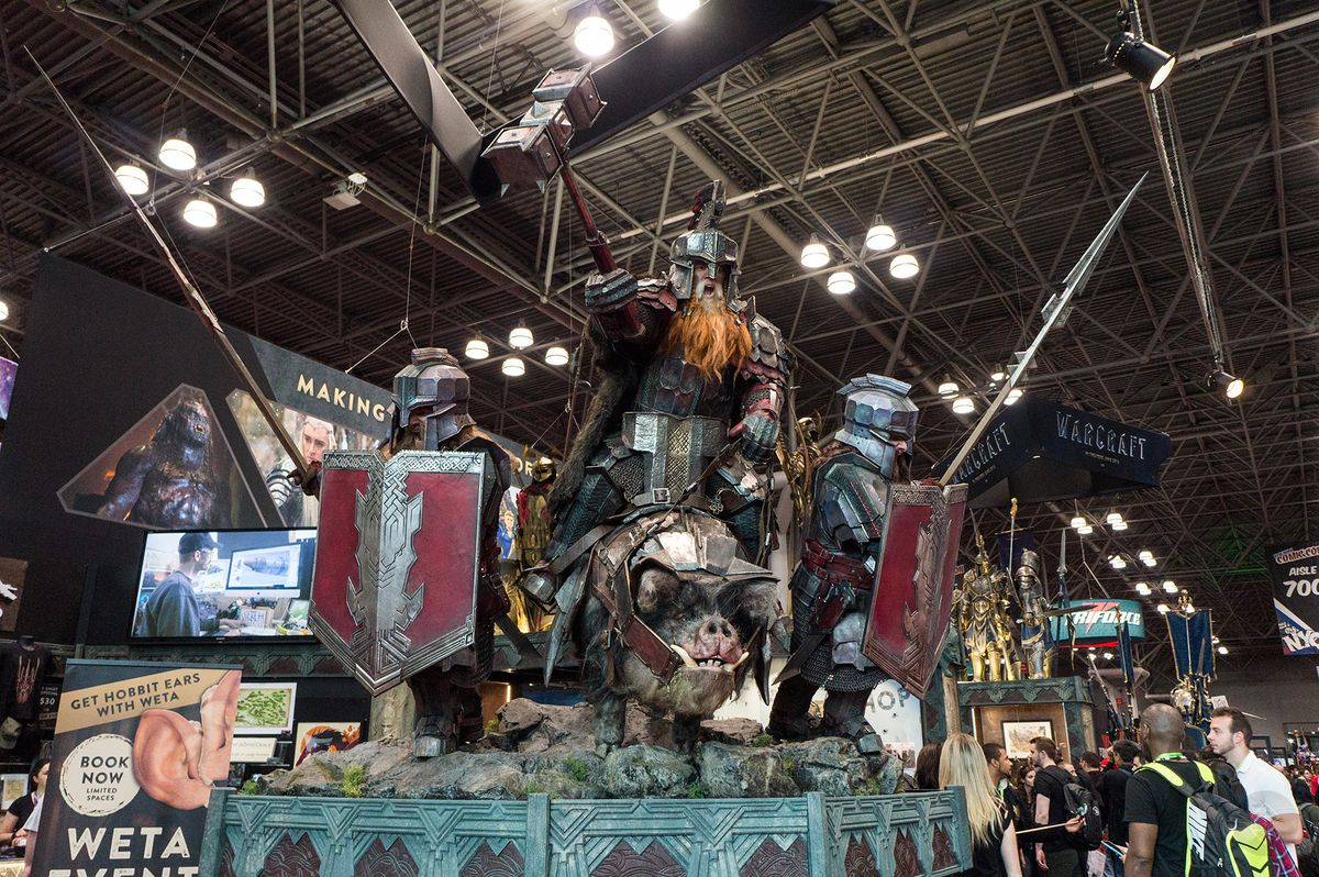 three dwarves outfitted for battle, with an armored boar in front of them, at the Weta Workshop booth at NYCC 2015