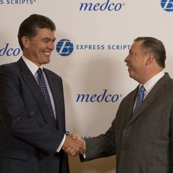 In this photo provided by Express Scripts, David Snow, CEO of Medco Health Solutions, left,  and George Paz, CEO of Express Scripts, shake hands Thursday July 21, 2011, after conclusion of negotiations to merge the two companies.  The new company will be known as Express Scripts with headquarters in St. Louis, Mo.