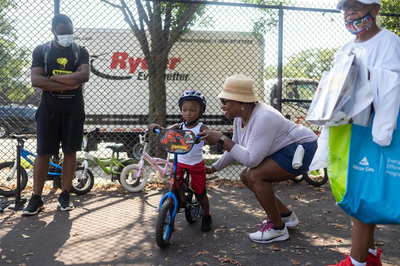 Darlena Burnett teaches Narsir Arnold to ride a bike during a bike giveaway and bicycle safety camp event at Union Park Saturday morning, Aug. 8, 2021.