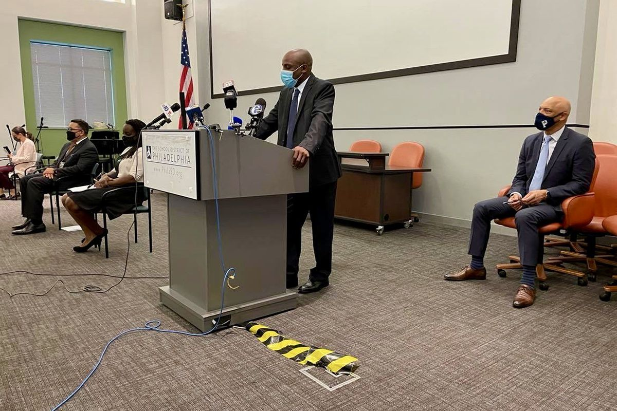 """Ryan """"Smitty"""" Smith, standing, is a safety officer at Kensington Health Sciences Academy. To the right is Philadelphia Superintendent William Hite."""