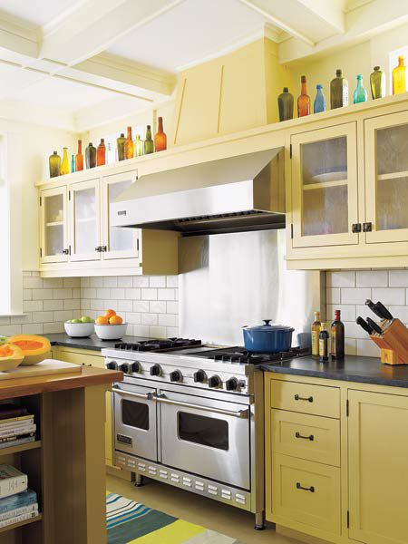 Stainless Steel Hood Vent Above Double Range In Yellow Kitchen