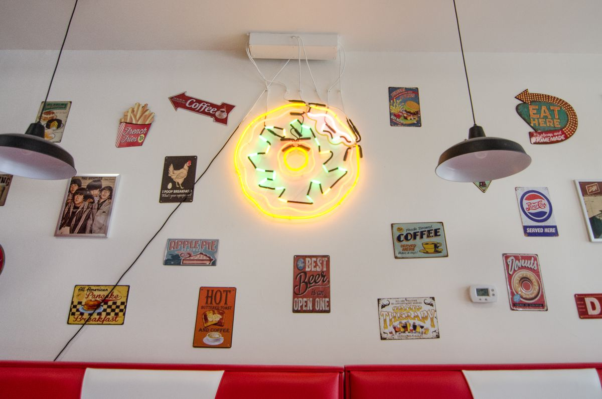 A white wall of a restaurant is decorated with vintage diner-themed signs and a neon doughnut. The tops of red and white booths are visible at the bottom of the photo.