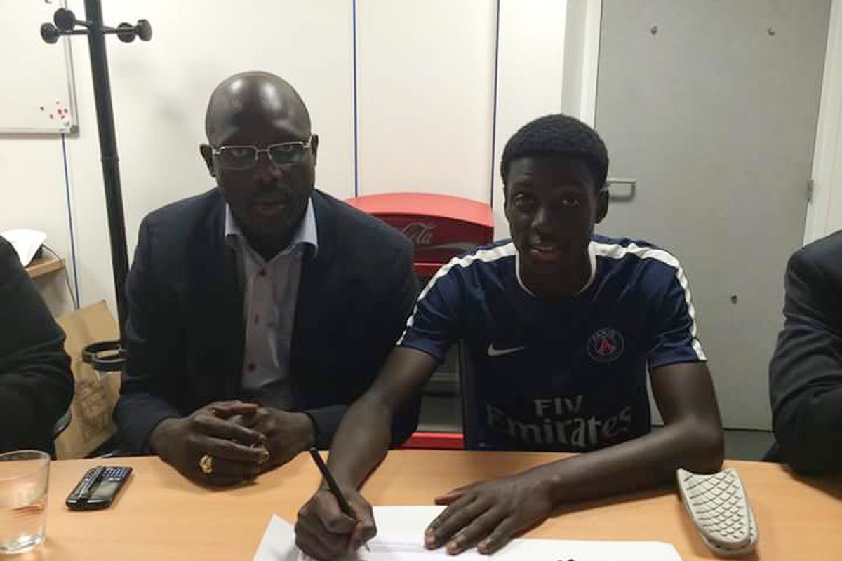Timothy Weah (r) signs an academy deal with Paris St. Germain while father George (l) looks on.