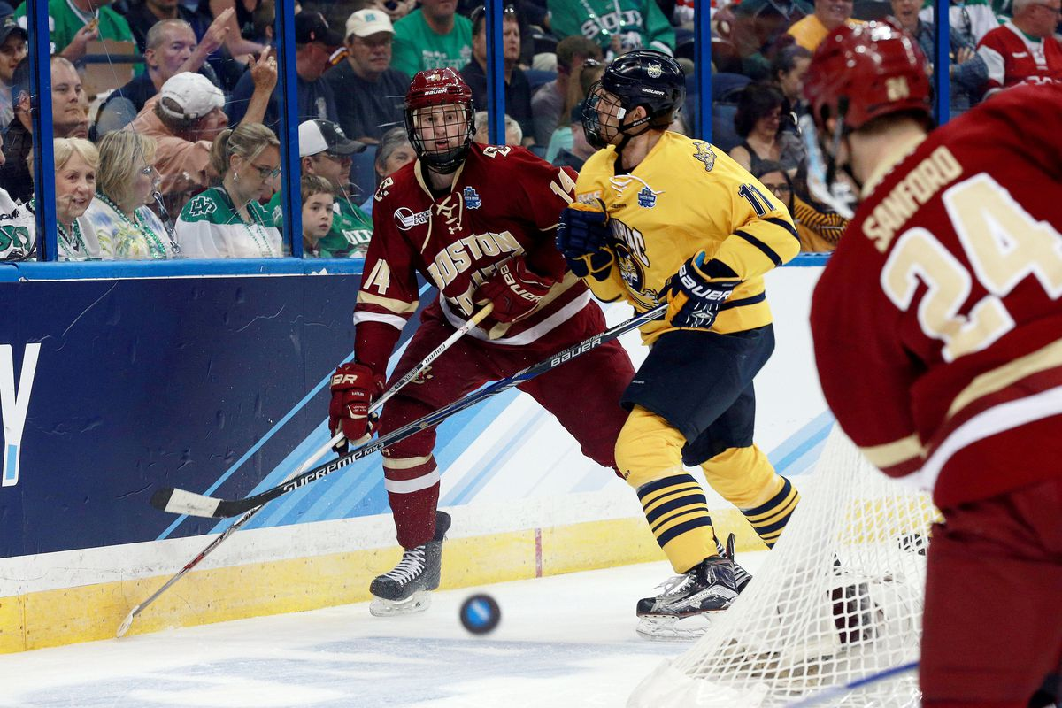Adam Gilmour (14) fights for a loose puck with Quinnipiac's Tim Clifton in the NCAA Frozen Four.